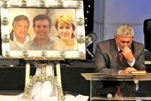 A mourner sits next to a picture of Martin, Rudi and Teresa during the memorial service of the massacred family in Pretoria on Thursday  Image: Independent on Line