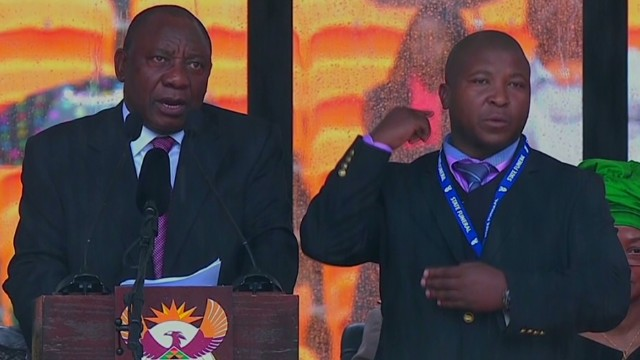 Standing next to the Deputy President of the African National Congress (ANC) Cyril Ramaphosa (left) is the mysterious sign language interpreter who has been accused of not being able to sign.  Image: CNN