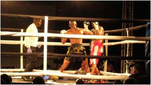 Themba Shicila throws a punch while referee Cliford Mbelu watches.