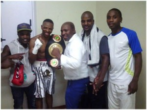 Mzonke posing with his title, flanked by his young corner. From right Simphiwe Tom, Felix Venganayi and tapiwaTembo