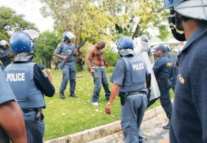 The state failed to prove that any of the police officers in this picture are guilty of using excessive force to kill Andries Tatane who is seen here topless and bleeding. The helmets worn by the officers make it difficult to conclusively say exactly who caused the fatal injuries. – image - africasacountry.com