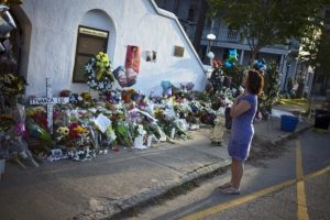 A woman stands in front of the church where people placed flowers in memory of the nine people who were shot on Wednesday.  Image: The Washington Post